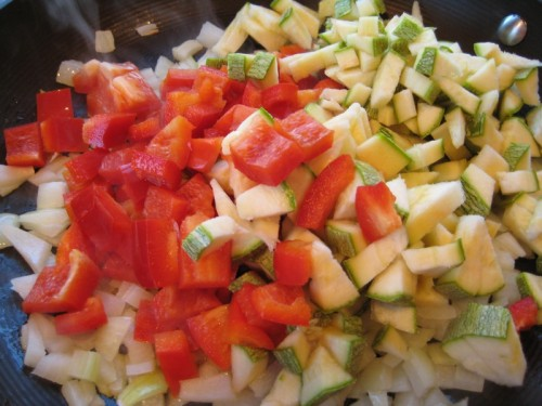 Add red peppers and squash to the onions.